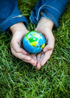 緑の芝生に対して地球を手で保持している少女