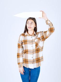 열린 입으로 빈 음성 화살표 포인터를 들고 어린 소녀. 무료 사진