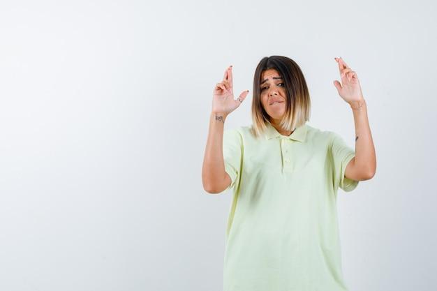 指を持った少女がtシャツを着て、心配そうに見えます。正面図。