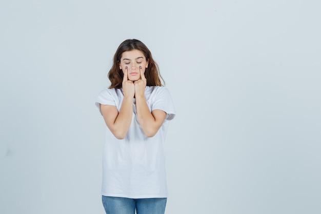 Молодая девушка держит пальцы на веках в белой футболке и выглядит разумно. передний план.