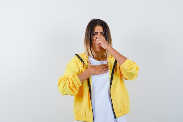 Молодая девушка держит кулак возле рта, чихает в белой футболке, желтой куртке и выглядит измученной, вид спереди.