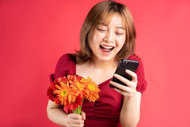 꽃을 들고 분홍색에 밝은 표정으로 전화를 사용하는 어린 소녀