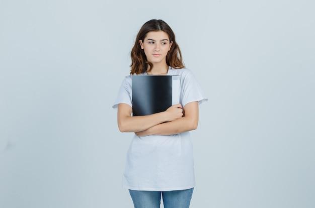 Маленькая девочка держит папку в белой футболке и смотрит задумчиво. передний план.