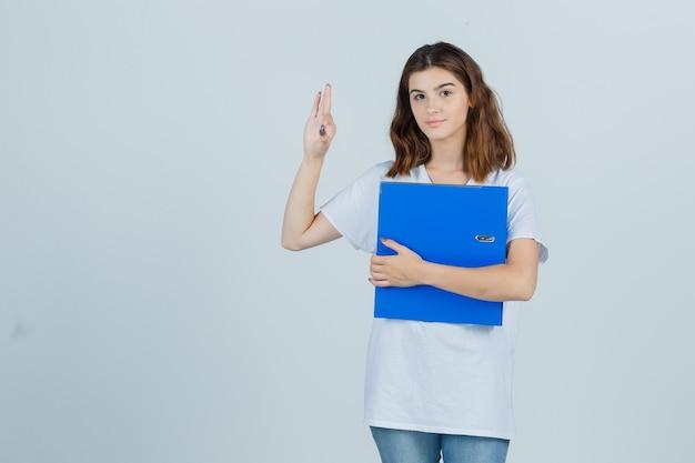 Молодая девушка, держащая папку, показывая нормальный жест в белой футболке и весело глядя, вид спереди.