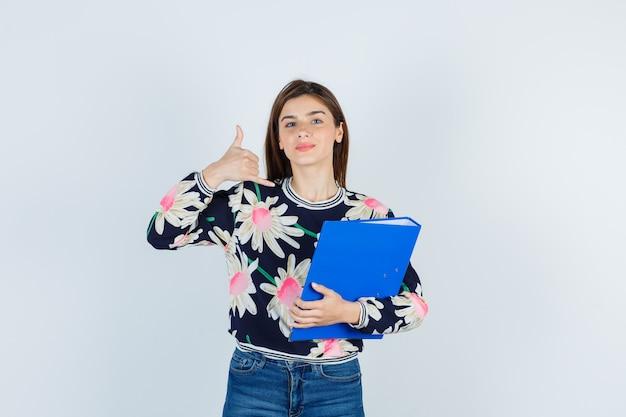 フォルダーを保持している若い女の子、花柄のブラウス、ジーンズで電話のジェスチャーを示し、自信を持って、正面図を表示します。