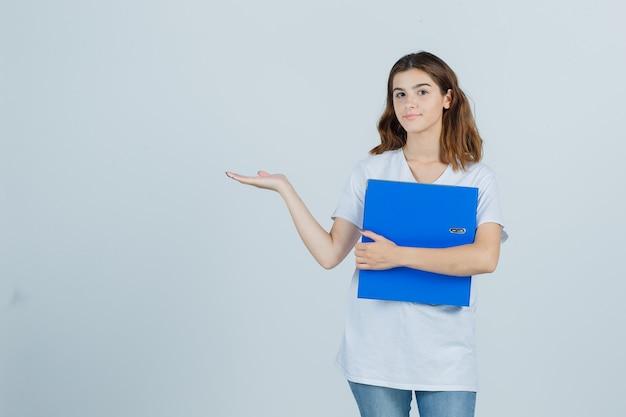 フォルダーを保持している若い女の子、白いtシャツで歓迎のジェスチャーを示し、自信を持って、正面図を表示します。