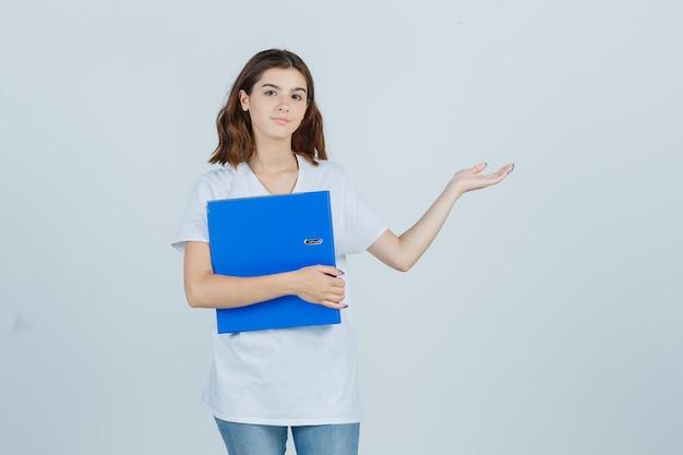 フォルダーを保持している若い女の子、白いtシャツで歓迎のジェスチャーを示し、陽気な、正面図を表示します。