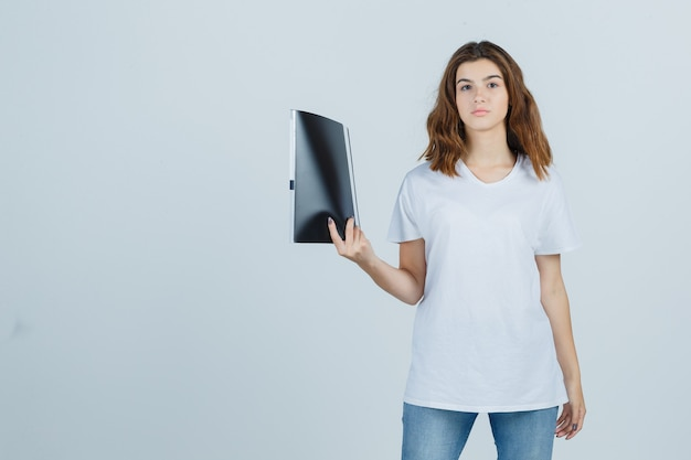 Young girl holding folder in white t-shirt and looking confident , front view.