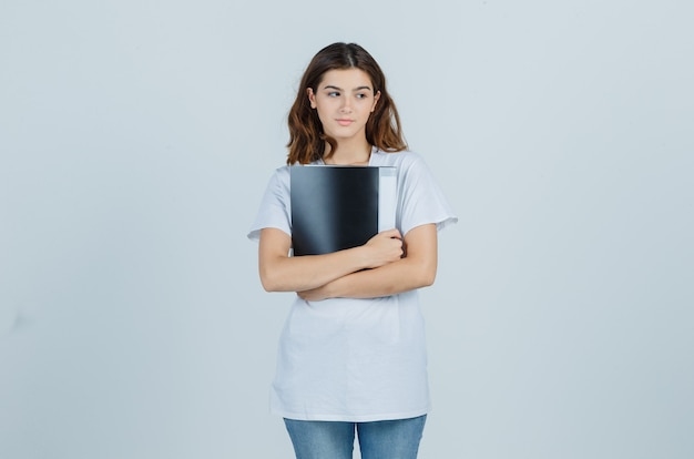 Young girl holding folder in white t-shirt and looking pensive. front view.