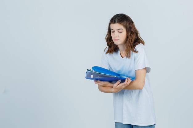Young girl holding folders in white t-shirt and looking focused , front view.