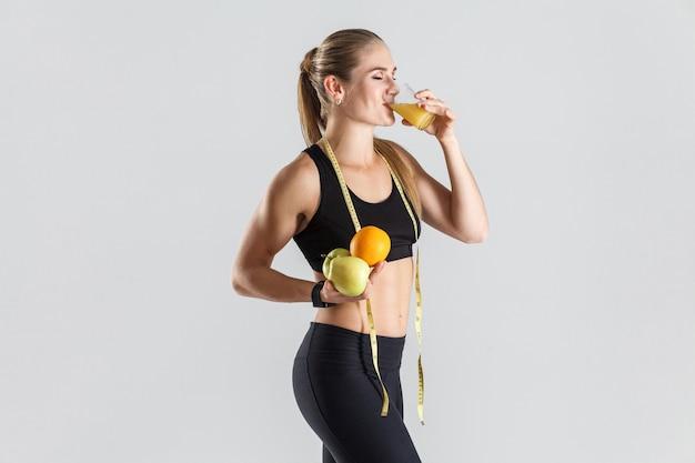 과일을 들고 오렌지 주스를 마시는 어린 소녀