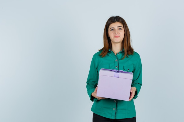Young girl holding gift box in both hands in green blouse, black pants and looking displeased. front view.