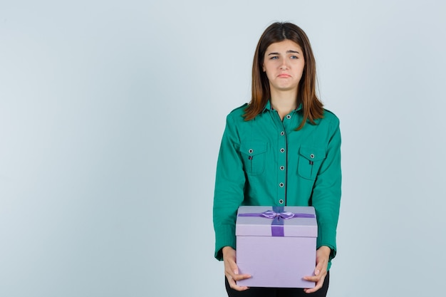 Young girl holding gift box in green blouse, black pants and looking disappointed. front view.