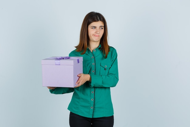 Young girl holding gift box in green blouse, black pants and looking displeased. front view.