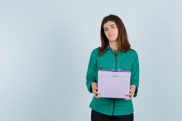 Молодая девушка держит подарочную коробку в зеленой блузке, черных штанах и угрюмо смотрит. передний план.