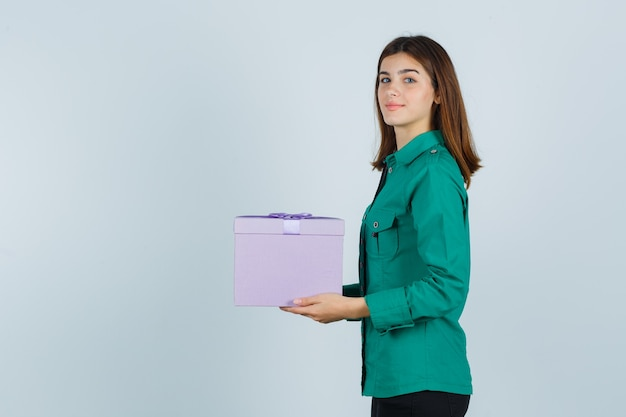 Young girl holding gift box, looking at camera in green blouse, black pants and looking cheery. front view.