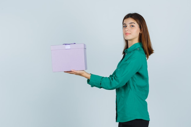 Young girl holding gift box, looking at camera in green blouse, black pants and looking happy , front view.
