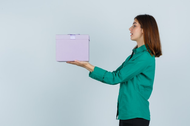 Young girl holding gift box, looking at it in green blouse, black pants and looking focused , front view.