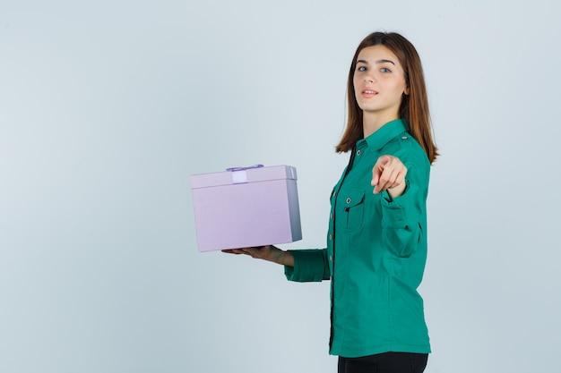 어린 소녀 선물 상자를 들고 녹색 블라우스, 검은 바지에 카메라를 가리키고 명랑 한 찾고. 전면보기.