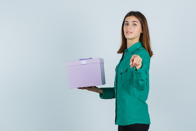 Young girl holding gift box, pointing at camera in green blouse, black pants and looking cheery. front view.