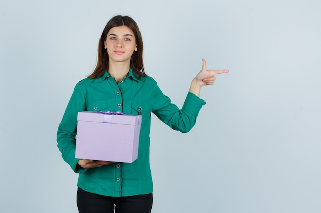 Young girl holding gift box, pointing right with index finger in green blouse, black pants and looking cheery , front view.