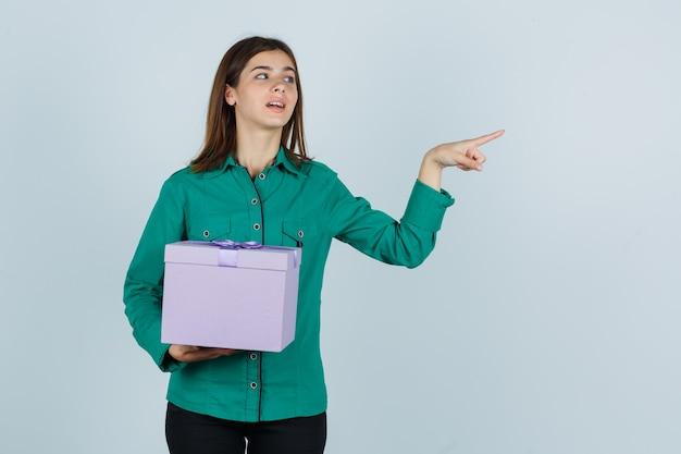 Молодая девушка держит подарочную коробку, указывая вправо указательным пальцем в зеленой блузке, черных штанах и смотрит сосредоточенно, вид спереди.