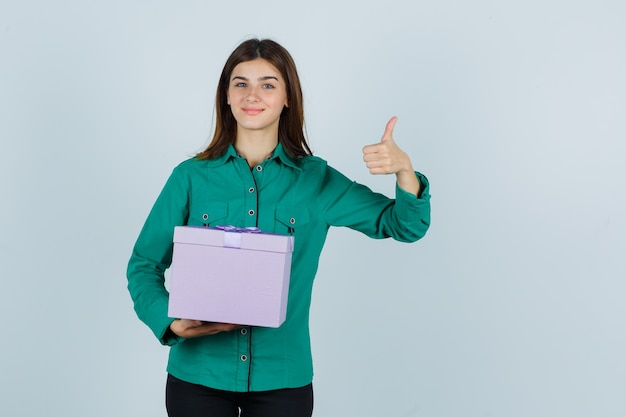 Young girl holding gift box, showing thumb up in green blouse, black pants and looking merry , front view.