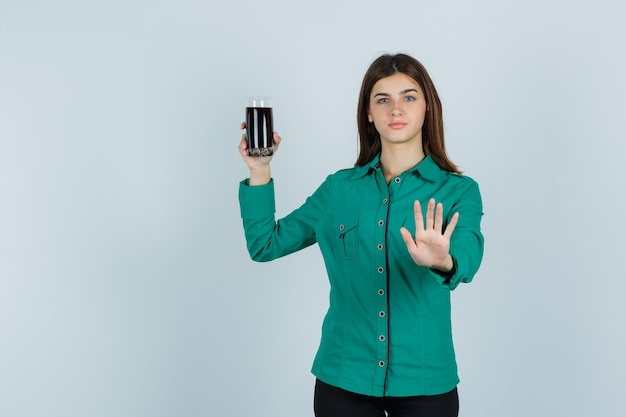Young girl holding glass of black liquid, showing stop sign in green blouse, black pants and looking serious. front view.