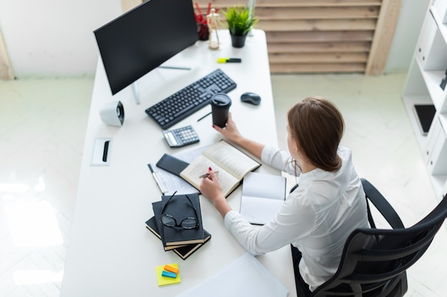 A young girl holding a glass of coffee and working in the office with books, computer and documents.