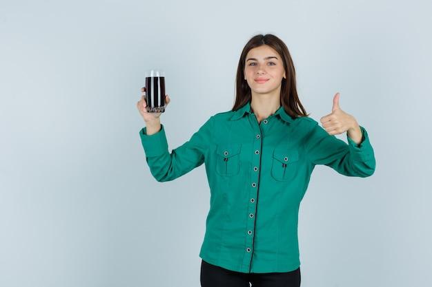 어린 소녀 검은 액체의 유리를 잡고 녹색 블라우스, 검은 바지에 엄지 손가락을 표시하고 행복을 찾고. 전면보기.