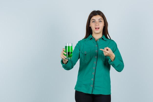 Молодая девушка держит стакан с зеленой жидкостью, указывая на нее указательным пальцем в зеленой блузке, черных штанах и выглядит удивленным. передний план.