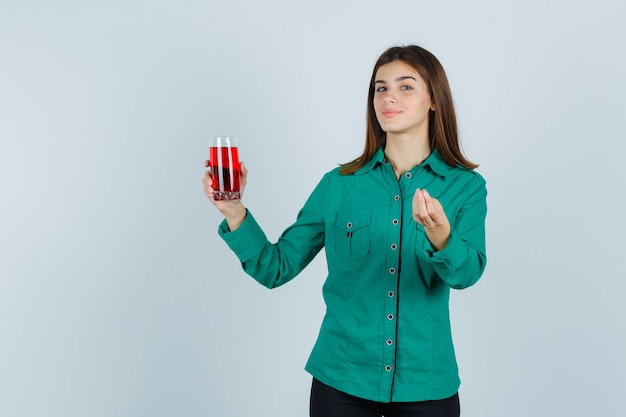 어린 소녀 빨간 액체 잔을 들고 녹색 블라우스, 검은 바지에 이탈리아 제스처를 보여주는 만족 찾고. 전면보기.