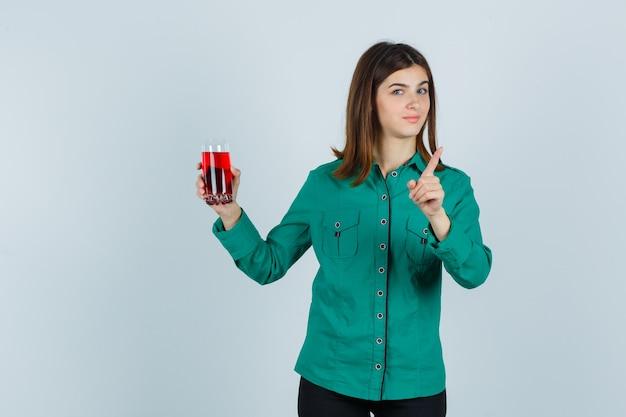 Молодая девушка держит стакан с красной жидкостью, показывая предупреждающий жест в зеленой блузке, черных штанах и выглядит мило, вид спереди.
