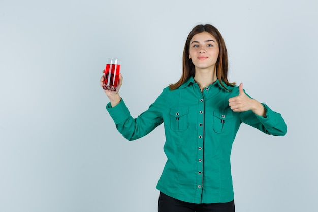 Young girl holding glass of red liquid, showing thumb up in green blouse, black pants and looking happy. front view.