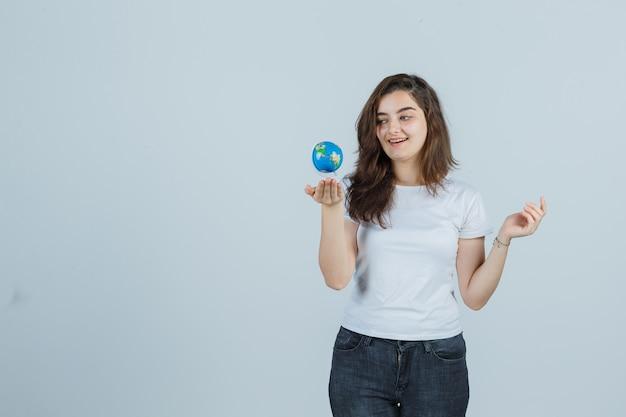 Молодая девушка держит глобус в футболке, джинсах и выглядит довольно. передний план.