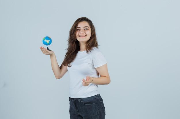 Tシャツ、ジーンズ、きれいに見えるカメラを見ながら地球を保持している少女、正面図。