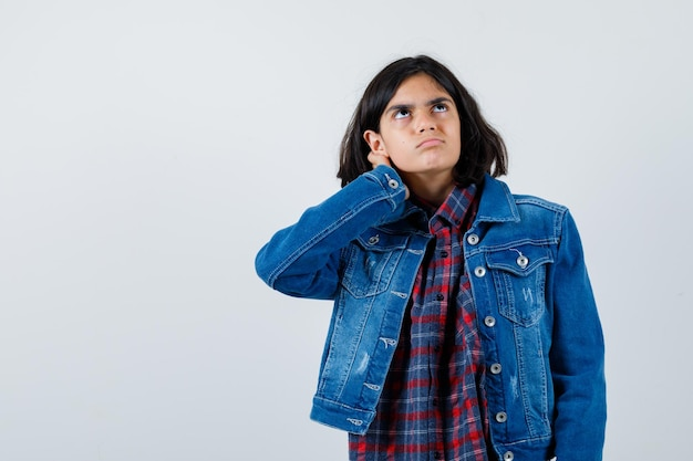 Giovane ragazza che tiene la mano sull'orecchio, guardando sopra in camicia a quadri e giacca di jeans e sembra pensierosa