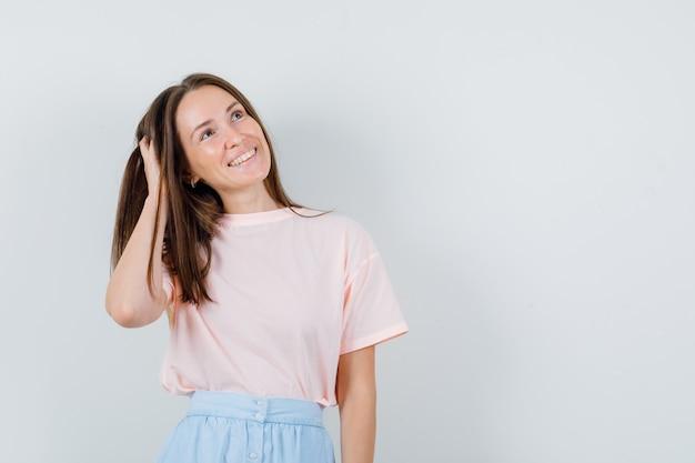 Tシャツ、スカート、希望に満ちた、正面図で髪に手をつないでいる若い女の子。