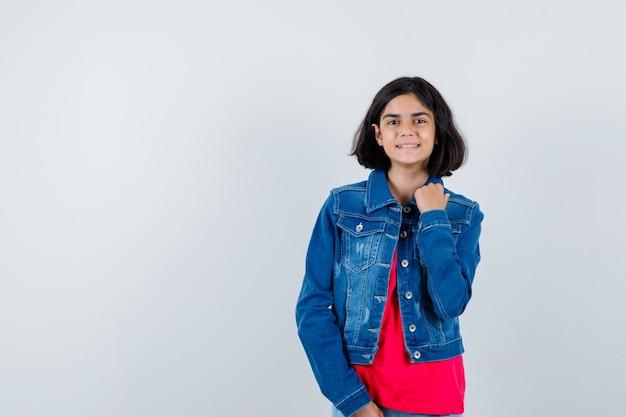Ragazza che tiene la mano sulla giacca in maglietta rossa e giacca di jeans e sembra felice, vista frontale.