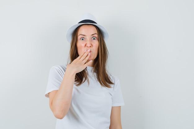 Ragazza giovane tenendo la mano sulla bocca in t-shirt bianca, cappello e guardando meravigliato, vista frontale.