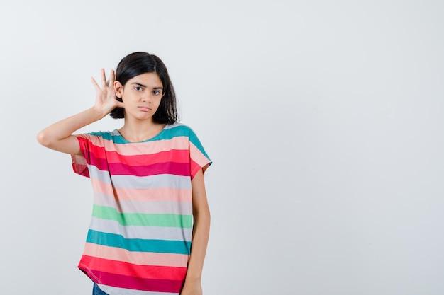 화려한 줄무늬 티셔츠를 입고 집중하는 모습을 듣기 위해 귀 근처에 손을 잡고 있는 어린 소녀. 전면보기.