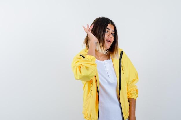 어린 소녀 흰색 t- 셔츠, 노란색 재킷에서 듣고 귀 근처 손을 잡고 초점을 맞춘, 전면보기를 찾고.