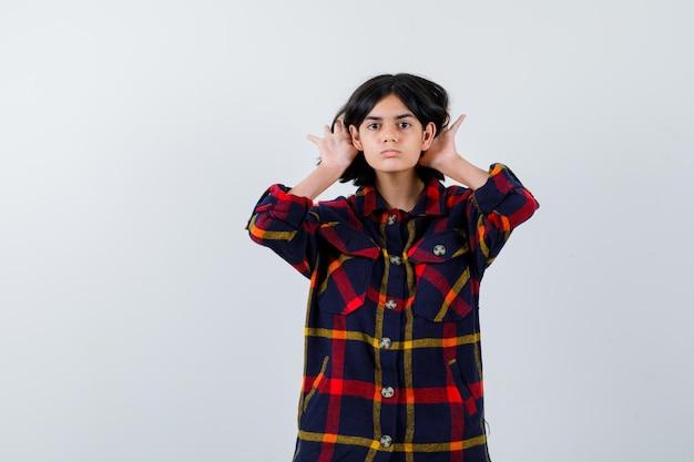 チェックのシャツで何かを聞くために耳の近くで手をつないで、焦点を当てているように見える若い女の子。正面図。