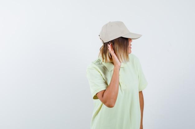 어린 소녀는 귀 근처에 손을 잡고 티셔츠와 모자를 듣고 초점을 맞춘 전면보기를보고 있습니다.