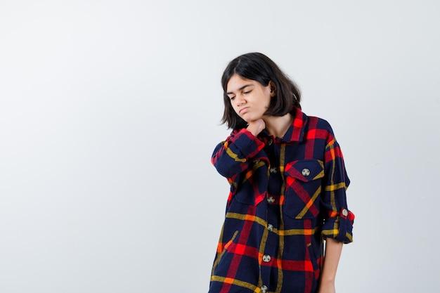 Giovane ragazza che tiene la mano sul collo, ha dolore al collo in camicia a quadri e sembra esausta, vista frontale.