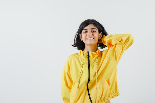 Ragazza giovane tenendo la mano dietro il collo in giacca bomber gialla e guardando felice.