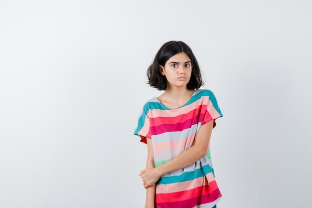 Молодая девушка держит руку на предплечье в красочной полосатой футболке и выглядит серьезным, вид спереди.