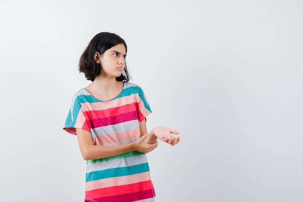 Молодая девушка держит руку на предплечье, глядя в красочную полосатую футболку и серьезно, вид спереди.