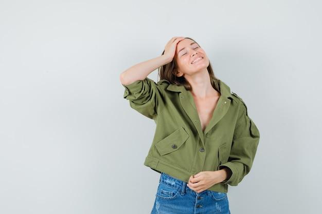 ジャケット、ショートパンツで額に手をつないで、幸せそうに見える少女、正面図。