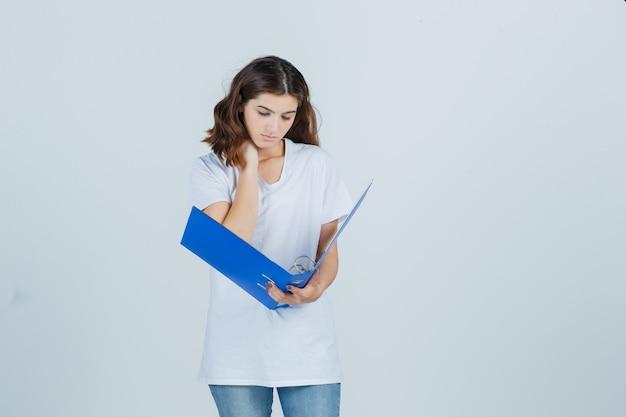 Молодая девушка держит руку на шее, смотрит в папку в белой футболке и выглядит занятой. передний план.